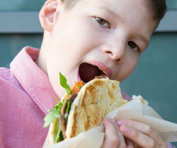 close-up, boy eating fast food, hamburger